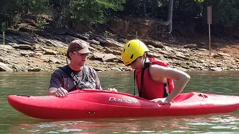 A man helping a teen in a kayak